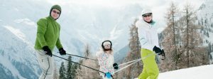 Family holding ski poles